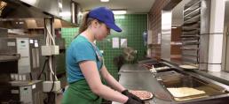 Tyttö valmistamassa pizzaa