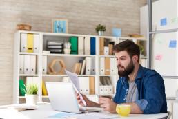Etämyynti käynnissä kotitoimistolla jossa mies tietokoneen äärellä kuulokkeet korvillaan
